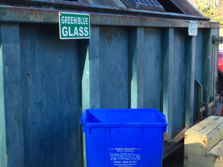 A smaller plastic recycling bin filled with glass in front of a much larger set of bins where glass is deposited at York County's Baxter collection center. Glass there is separated by color.