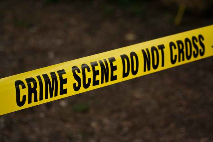 Yellow crime scene tape with black letters that spells out