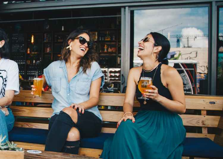 Two young women wearing sunglasses laugh while sitting on a bench and holding pints of craft beer outside a brew pub.