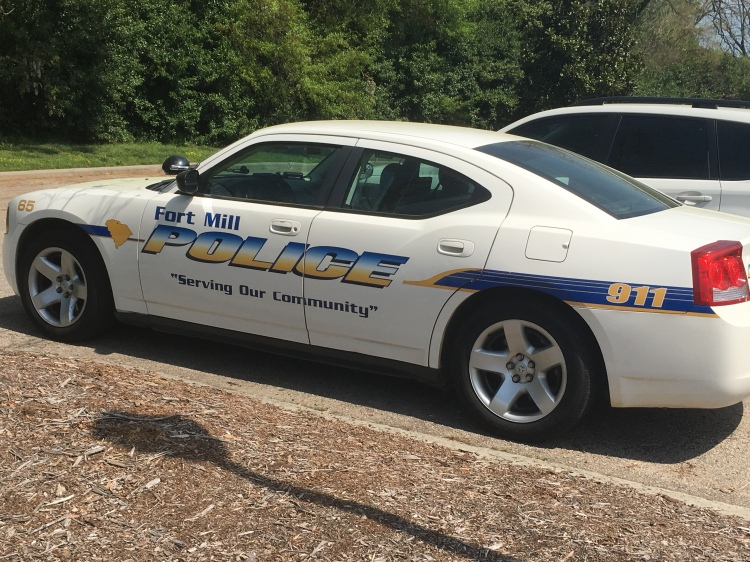 A Fort Mill Police Department patrol car parked near the station house.