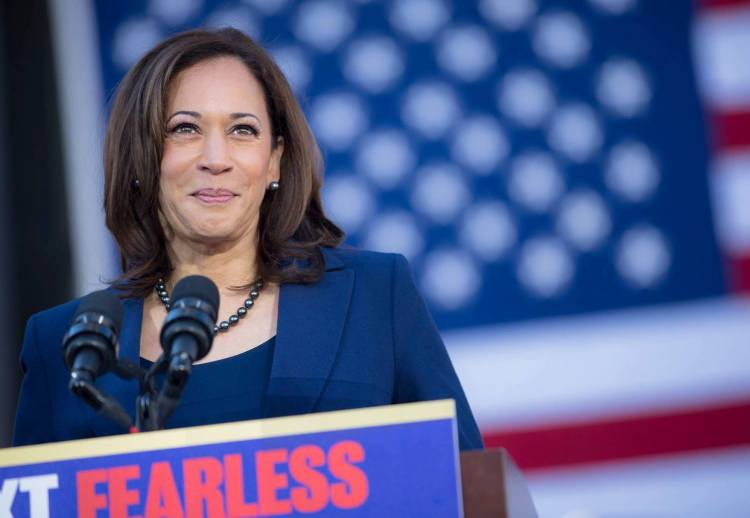 A smiling Kamala Harris in a blue blazer, stands in front of the red, white and blue U.S. flag in a campaign photo that is also posted on her Facebook page.
