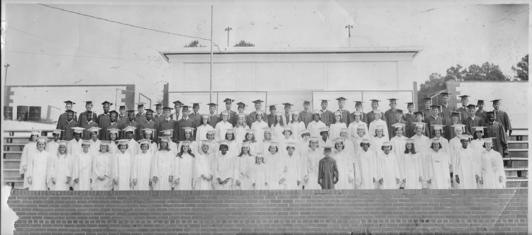 In a black and white image, members of the Fort Mill High Class of 1969 pose in the caps and gowns at graduation.