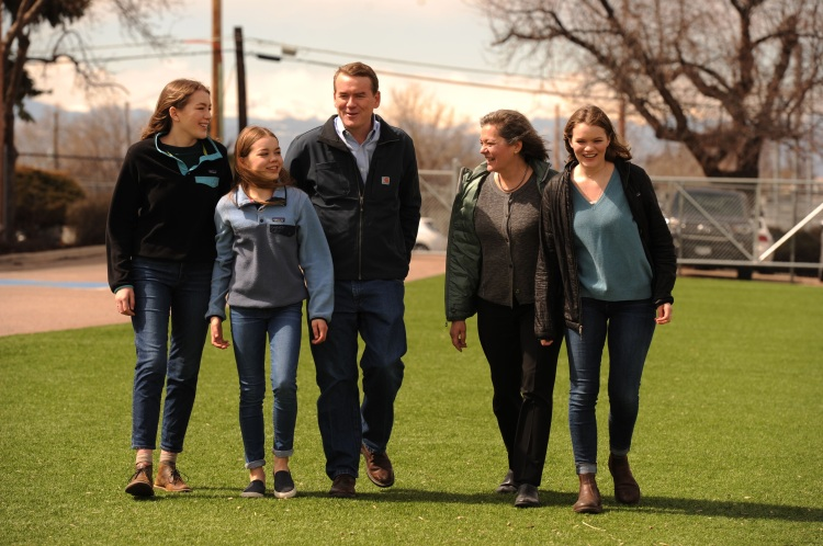 U.S. senator Michael Bennet, a candidate for president in 2020, walks with his wife and three daughters. They are outside, walking across a grass field and all are wearing jackets.