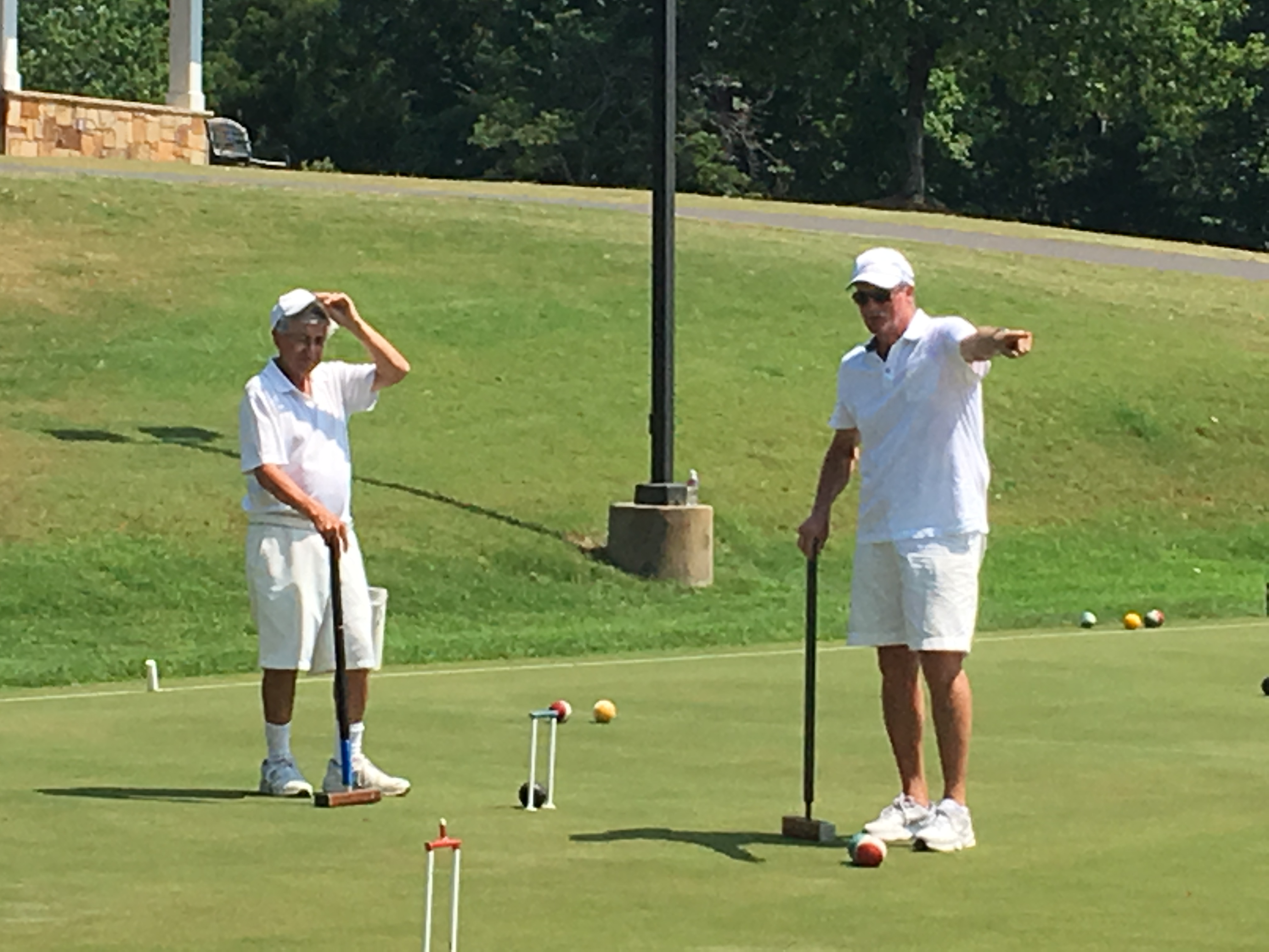 Two men in white shirts and shorts practice a version of croquet called six wicket at the Tega Cay court.