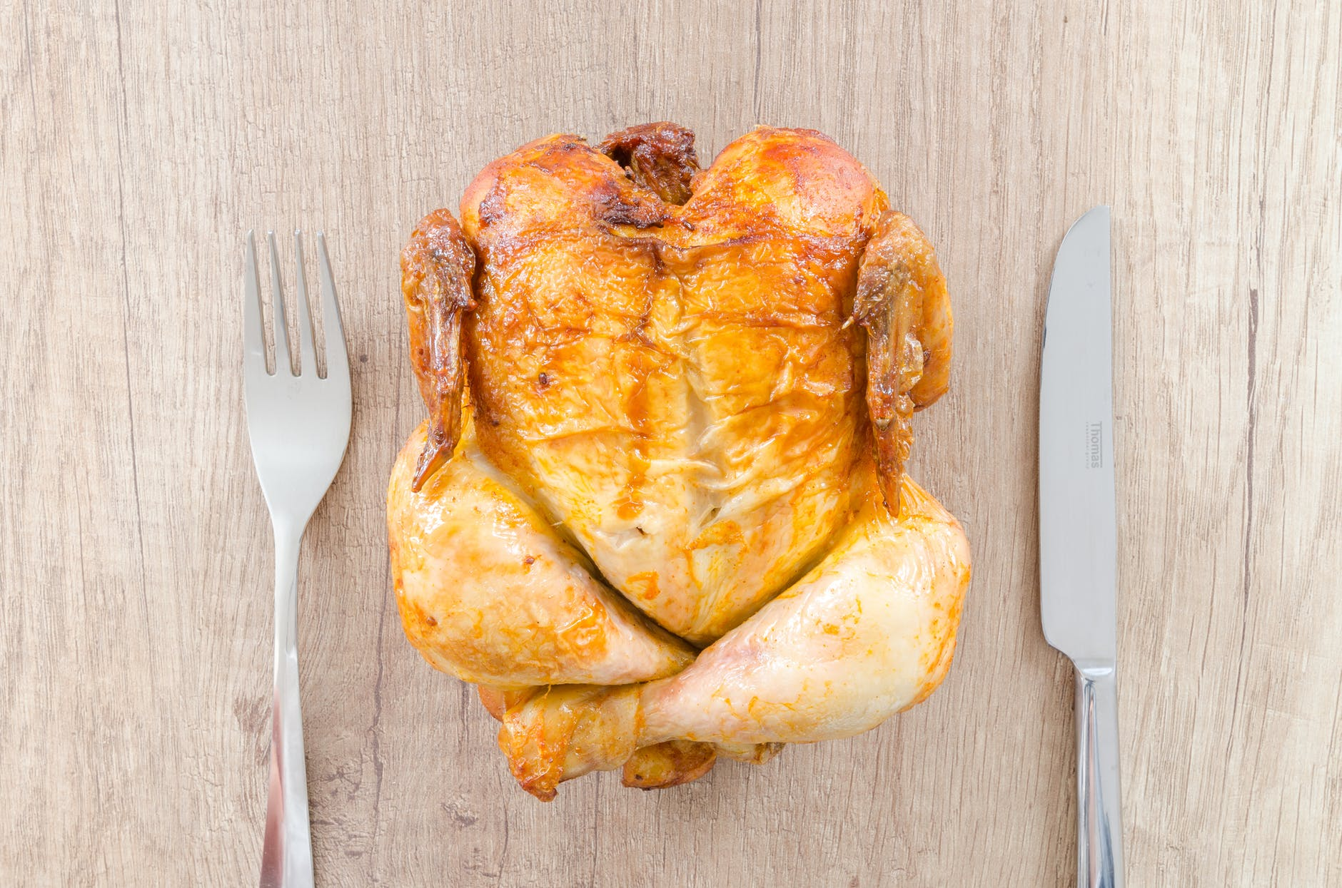 A golden brown roasted chicken on a slab of wood with a fork on the left side and knife on the right.