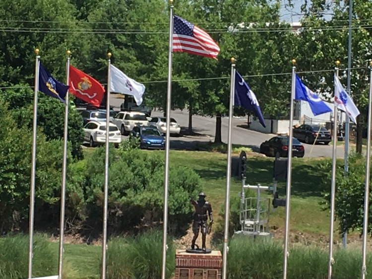 A look down into Veterans Park in Fort Mill. The U.S. flag is flanked by flags representing each branch of the U.S. Armed forces. In the background is a statue of a World War I Doughboy.